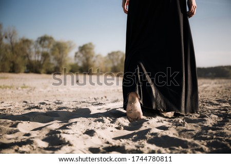 A woman walks into the distance on the sand with her bare feet. A black and white photo of a part of a person's body with a mood of depression, anxiety, sadness and loss.