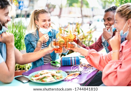 Friends drinking spritz at cocktail bar with face masks - New normal friendship concept with happy people having fun together toasting drinks at restaurant - Bright end filter with focus on left woman #1744841810