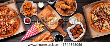 Table scene of assorted take out or delivery foods. Hamburgers, pizza, fried chicken and sides. Top down view on a dark wood banner background.