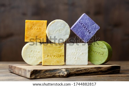 Traditional organic turkish handmade colored soap bars with different ingredients on a brown wooden background.  Titles in turkish meaning saffron, lavender, laurel,hood,olive oil and donkey milk