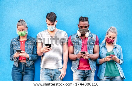 Multiracial friends with face masks using tracking app with mobile smart phones - Young milenial people watching content on social media networks - New normal lifestyle concept - Bright vivid filter #1744888118