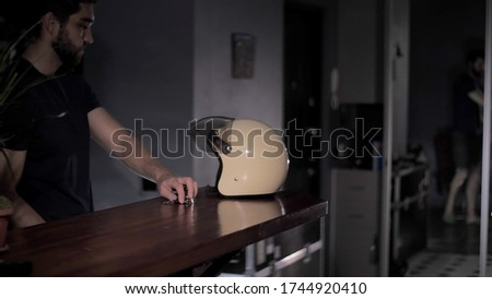 On the bar is a motorcycle helmet and keys. Biker takes a motorcycle helmet and keys for a motorcycle from a bar counter and sets off on a journey. #1744920410