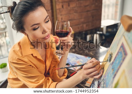 Attractive young woman holding glass of alcoholic drink and drawing picture with paints in home art studio