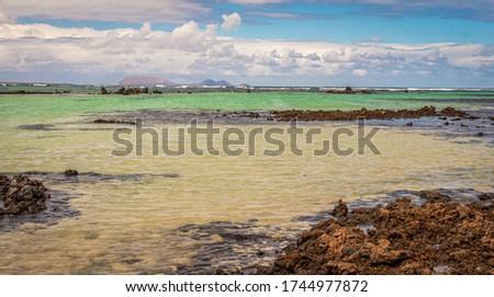 White sand and black lava rocks at Caleton Blanco beach, Lanzarote, Canary Islands, Spain. Volcanic beach of Lanzarote Island, Canaries, Spain