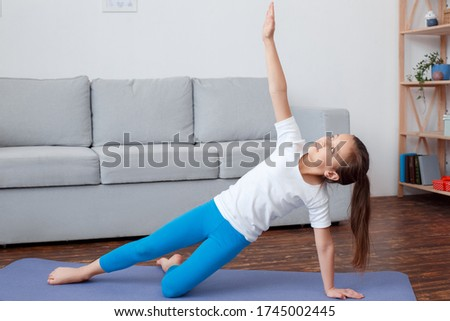 Goods store advertises sports equipment at home. Yoga mat, dumbbells, ball, online health programs. Young girl, teenager standing in gymnastic pose on the floor. Horizontal picture with copy space.