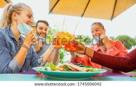 Friends drinking coktail and eating snack tapas in a restaurant bar outside in summer days with face mask on to be protected from coronavirus - Happy people cheering with spritz and having fun  #1745006042