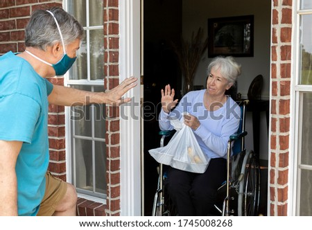 A church volunteer wearing a mask brings food to an elderly woman in a wheelchair that may otherwise be unable to get groceries during COVID19. Royalty-Free Stock Photo #1745008268