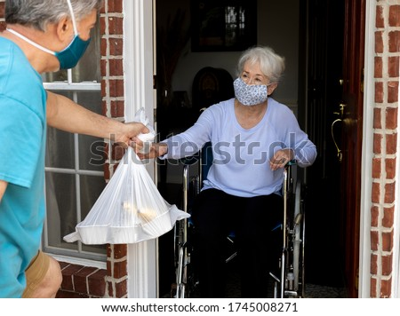 A volunteer wearing a mask brings food donation to an elderly handicapped woman in a wheelchair during COVID19. Royalty-Free Stock Photo #1745008271