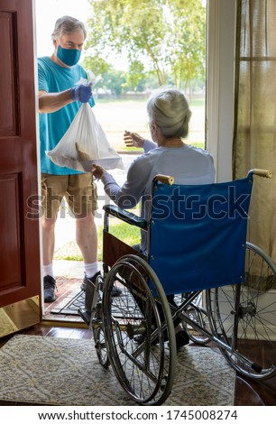 A man wearing a mask working with a church group or other benevolent organization brings some groceries to an elderly woman in a wheelchair. Royalty-Free Stock Photo #1745008274