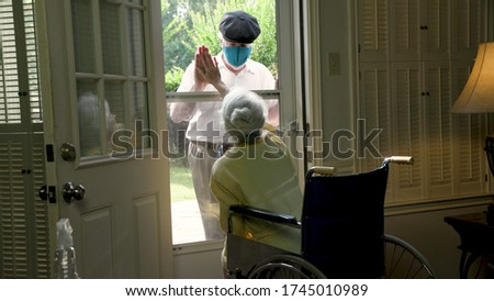 An elderly woman in a wheelchair social distancing because of COVID19 visits with a caring relative or neighbor through her glass storm door. Royalty-Free Stock Photo #1745010989