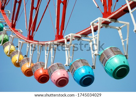 Close-up of a ferris wheel, taken from the ground. The cabins are each of different colors, imitating those of a rainbow, making it a colorful picture with a blue sky background.