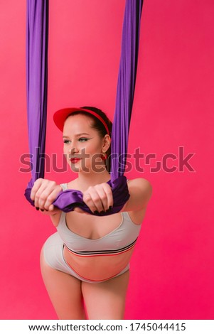 Vertical picture portrait sexy attractive strong sport young womant gymnast hold on air silk stretching and looking aside isolated over pink vivid background