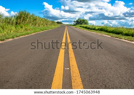 Parallel lanes that signal the location of prohibited overtaking on a paved side road Royalty-Free Stock Photo #1745063948