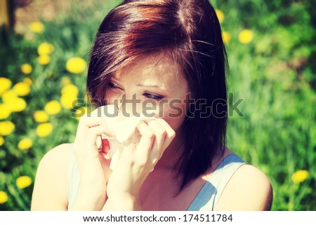 Young woman in summer dress standing on meadow during sunny day  and wiping her nose. Girl with runny nose, having allergy and holding a tissue next to her face. #174511784
