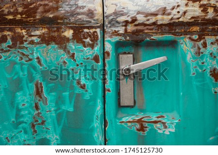 Poor quality paint on the car, cracks and scratches on the rusty metal surface. Abstract pattern, texture, pattern detail background with rusty stains. A car door handle on an old green car