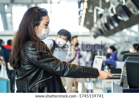 Asian female traveler giving passport to customer check in officer at airline service counter. Woman wearing face mask when traveling by airplane transportation to prevent covid19 virus pandemic. #1745159741