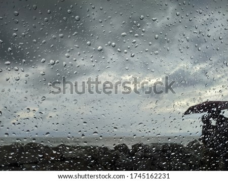 Couples in an umbrella , Photo from inside a car through window glass. Raindops on the window glass makes the unexpected photo wonderful Love , Rain and Beach side complete romatic attire