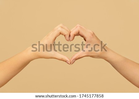 Love. Female Hands Making Heart Shape For Staying Positive During COVID-19 Outbreak. Caucasian Woman Folding Fingers And Palms As Romantic Symbol Against Beige Background.