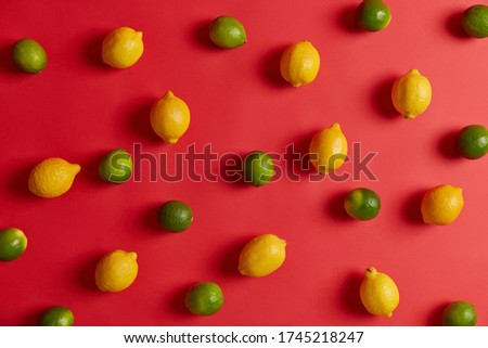 Collection of yellow lemons and green limes ready for sale on market, isolated over red studio background. Refreshment and sour flavor. Summer time and edible citrus fruits concept. Viramin C. #1745218247