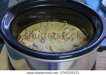 View of slow cooker chicken pot pie to be served with hot biscuits on the side. Crock pot chicken pot pie.