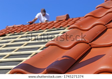 Roofing work, new covering of a tiled roof Royalty-Free Stock Photo #1745271374