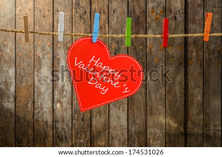 Cute big red heart hanging on the clothesline. On old wood background. #174531026