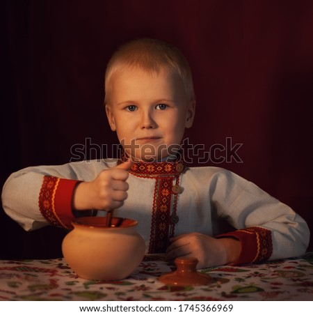 a boy in a Russian folk costume at a table with porridge in a clay pot. Style Of Russia. Traditional Russian costume. Russian shirt. tradition of Russia. Historical Russian image. #1745366969
