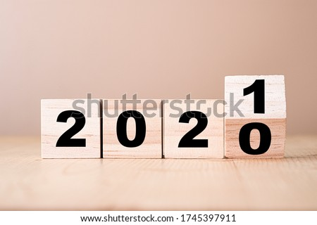 Hand flipping wooden blocks for change year  2020 to 2021 . New year and holiday concept. Royalty-Free Stock Photo #1745397911