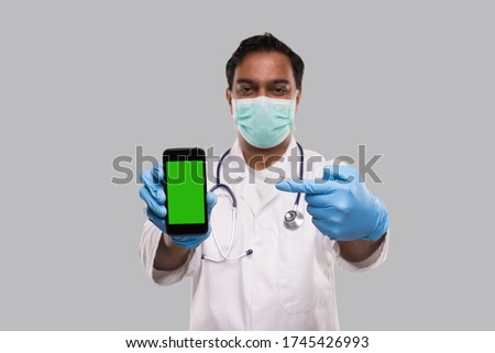 Doctor Pointing at Phone Wearing Medical Mask and Gloves. Indian Man Doctor Technology Medicine at Home. Phone Green Screen Isolated