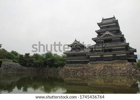 Matsumoto Castle In the city of Matsumoto Of Japan. This picture has green trees, white skies, black castles.