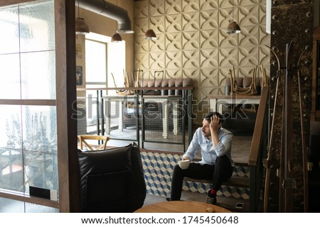 Restaurant, cafe, bar closed due to COVID-19 or Coronavirus outbreak lockdown, stressed owner of small business, depressed, despair. Businessman exhausted, upset. Business, economy, finance crisis. Royalty-Free Stock Photo #1745450648