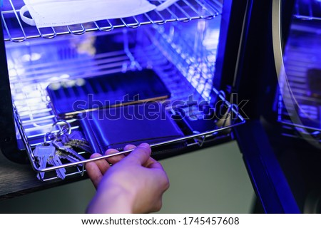 UV light sterilization of mobile phone and  face mask to disinfection. COVID-19 prevention concept. ultra-violet sterilization and disinfection. Royalty-Free Stock Photo #1745457608