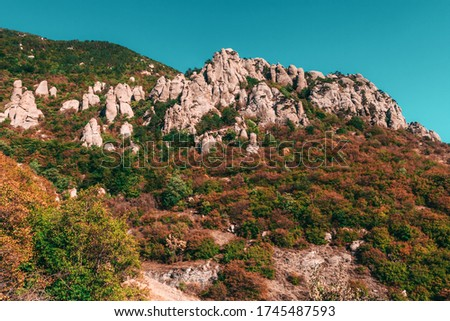 Mountain bottom of Mount Demerdzhi, view of the Valley of Ghosts at sunset. Natural sight of Crimea. Geological limestone weathering. Erosion of rocks. Amazing rocky landscape with blue sky #1745487593
