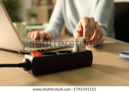 Close up of woman hand plugging plug on a power strip socket at night using laptop on a desk at home Royalty-Free Stock Photo #1745541515