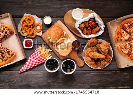 Table scene with large variety of take out and fast foods. Hamburgers, pizza, fried chicken and sides. Above view on a dark wood background. #1745554718