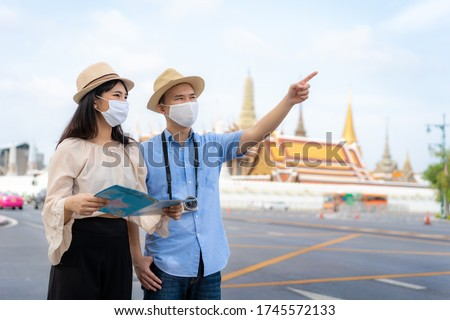 Asian couple happy tourists to travel wearing mask to protect from Covid-19 on they holidays and holding travel map and pointing in Wat Phra Kaew Temple in Bangkok, Thailand #1745572133