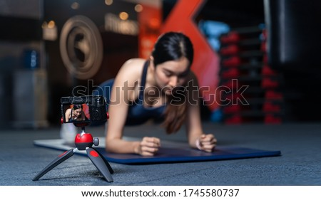 The camera on the tripod is taking pictures or videos. Asian Women Trainer In Good Shape Teaching or performing a sample of plank poses is a bodyweight exercise in online training concept
