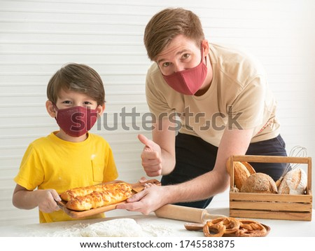 Young father and his son wearing face masks while baking bread at home.Stay at home , Social distancing concept. Royalty-Free Stock Photo #1745583875