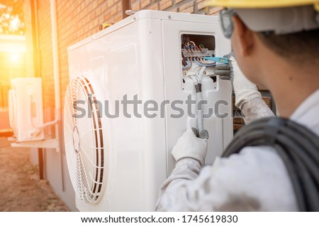Air Conditioning Technician and A part of preparing to install new air conditioner. Technician vacuum pump evacuates and checking new air conditioner Royalty-Free Stock Photo #1745619830