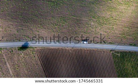 Parallel lines from an aerial view of farm land and a dirt road. drone picture of gravel road that splits two field. Agriculture field and from above with the road in middle