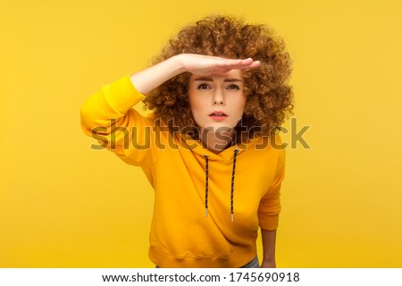 Portrait of curious curly-haired woman in urban style hoodie holding hand above eyes and peering into distance, looking far away, expecting and searching someone on horizon. studio shot isolated #1745690918