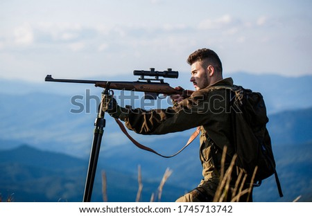 Hunter with hunting gun and hunting form to hunt. Hunter is aiming. The man is on the hunt. Hunt hunting rifle. Hunter man. Shooter sighting in the target. Hunting period. Male with a gun. #1745713742