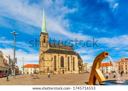 St. Bartholomew's Cathedral in the main square of Plzen with a fountain on the foreground against blue sky and clouds sunny day. Czech Republic, Pilsen. Famous landmark in Czech Republic, Bohemia. #1745716553