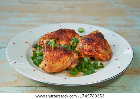 Close up Picture on vintage plate with traditional czech style roasted tasty and spicy chicken legs sprinkler with chopped fresh spring onion. Delicious balanced low calorie food full of nutritions.