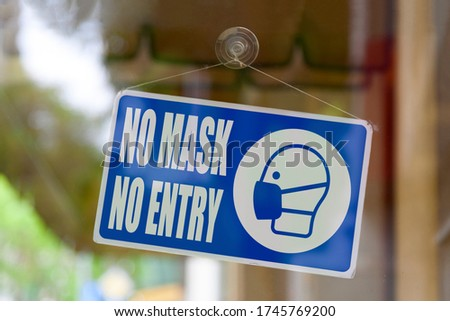 "Close-up on a blue closed sign in the window of a shop displaying the message ""No mask, no entry"". #1745769200"