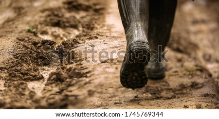 Dirty farmer's rubber boots walking on the rainy road. Royalty-Free Stock Photo #1745769344