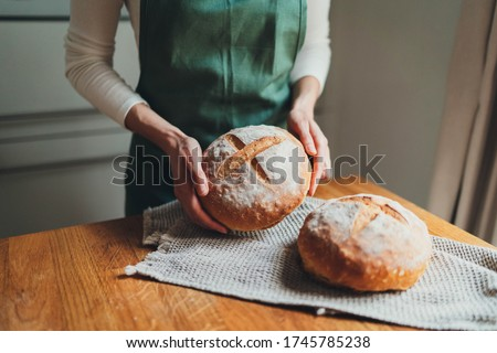 Woman in green linen apron holding homemade sourdough bread, Cooking at home, Homemade country bread loaf Royalty-Free Stock Photo #1745785238