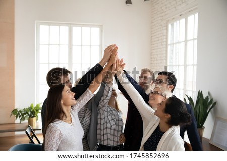 Overjoyed different ages mixed race teammates raising joined hands, giving high five to each other, celebrating company business success achievement, involved in team building activity in office. Royalty-Free Stock Photo #1745852696