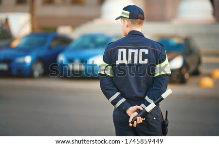 Inspector of traffic police in uniform with sign DPS (inscription - Department of traffic police) on duty . Traffic police Inspector enforcing traffic safety compliance on roads and highways #1745859449