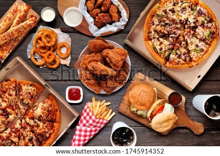 Buffet table scene of take out or delivery foods. Pizza, hamburgers, fried chicken and sides. Above view on a dark wood background.